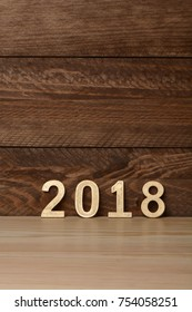 New year two thousand and eighteen in golden wood letters on wooden background, 2018
