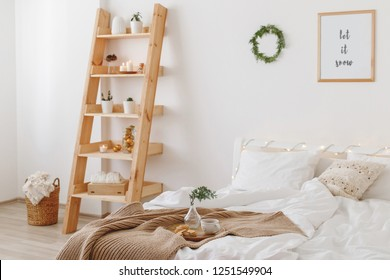 New year winter home interior decor. Christmas holiday decorated room. Stylish cozy bedroom: bed, wooden shelving, wicker basket, knitted blanket, plaid, wreath of pine branches, led garland lights.
