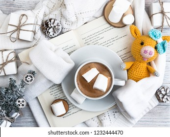 New Year Yellow pig 2019.A cup of coffee with marshmallows stands on the open book. A warm sweater. New Year's and Christmas. Christmas tree and gifts of jewelry, bracelets with charms. Huggy concept.