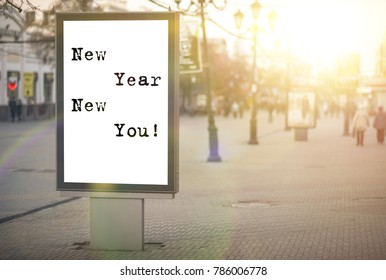 new year new you! text on an advertising banner, city street, sun rays