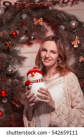 New Year young Girl with holiday mood in Christmas interior with tree and funny decorative toys. Beautiful woman portrait in sweater and decor in arms. Copy free space for text. 2017 trend