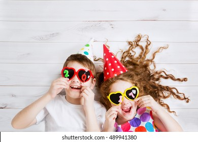 New Years 2017, christmas holiday. Funny children with sunglasses heart shape, hold 2017 candles, lies on the wooden floor. High top view.