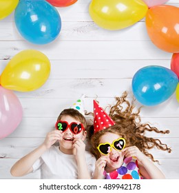 New Years 2017, christmas holiday. Funny children with sunglasses, hold 2017 candles, lies on the wooden floor. High top view.