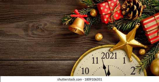 New Year's 2021 Eve. Retro style clock with christmas decorations and gifts on brown wooden background. Last moments before Christmas or New Year
