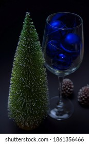 New Year's attributes - a tree and a glass filled with blue balls, stand on a black background. behind the glass are two candles in the shape of New Year's cones. shooting with artificial light