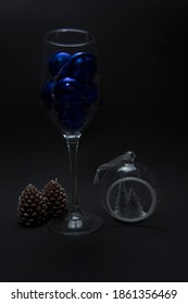 New Year's attributes - two candles in the shape of cones and a beautiful New Year's ball are standing near a glass filled with blue Christmas balls on a black background. filmed under artificial ligh