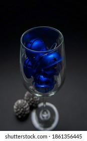 New Year's attributes - two cone-shaped candles stand near a glass filled with blue Christmas balls against a black background. filmed under artificial light