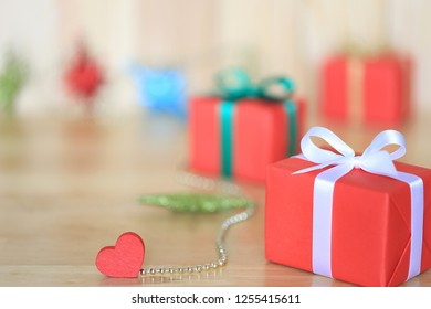 New Year's background for Christmas or Greeting season, Red gift box with white ribbon and red heart on wooder background