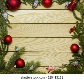 New Year`s border, frame from Christmas tree fir branches, silver pine cones, red balls on old wooden desk table background. Big copyspace for holiday congratulations.
