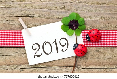 New Years card  for 2019 with leafed clover and ladybugs on wooden background