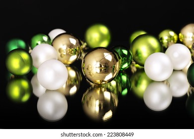 New Year's and Christmas ornaments, balls of white, gold and green on a mirror in front of a black background/New Year's and Christmas ornaments
