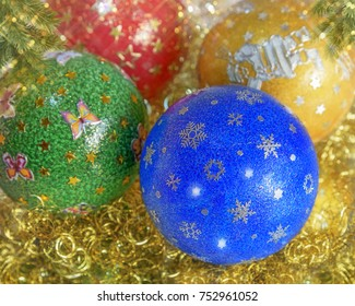 New Year's, Christmas still life. Handmade decorated green, red, blau, yellow balls on the gold tinsel. Horizontal. Close up
