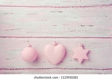 New Year's Christmas toys, heart, star and ball on a beautiful wooden pink table