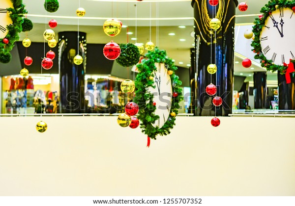 The New Year's clock is decorated with green branches and hangs on a rope in a store in a shopping center and foreshadow the coming of the new year.
