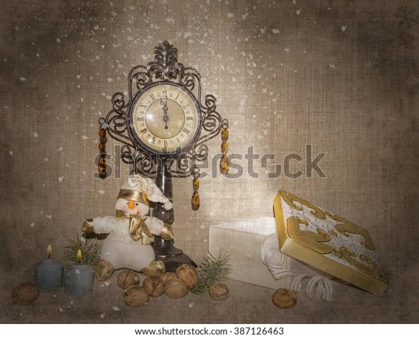Новогодняя композиция.  Рождественский подарок.  Снеговик сидит под часами.  Орехи и свечи.  Подарок со снегом.