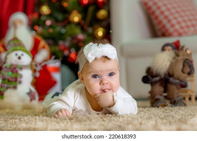 New Year's Concept. Adorable little girl near a Christmas tree with presents. with finger in the mouth new year