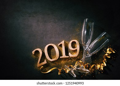 New Years Eve or Birthday celebration. Two champagne glasses with numbers 2019 and streamers on dark background