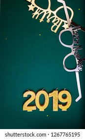 New Years Eve celebration background , 2019 number made with golden glitter candles, flatlay over a green board, luxury  holiday concept, with funny party glasses.
