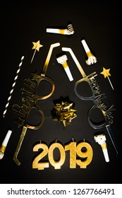 New Years Eve celebration background , 2019 number made with golden glitter candles and decorations, flatlay over a black board, luxury  holiday concept, with funny party glasses.