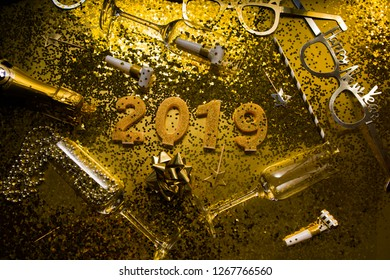 New Years Eve celebration background with champagn glass, 2019 number made with golden glitter canles, christmas decoration around, flatlay over a golden board, luxury  holiday concept