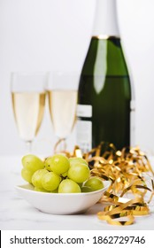 New Years Eve celebration concept background. Closeup of grapes with champagne bottle and two glasses blurred on the background on marble table. Selective focus,blurred background