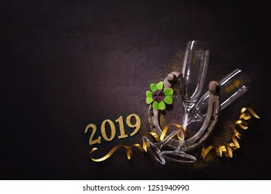 New Years Eve celebration. Two champagne glasses with a horseshoe and shamrock as lucky charm on dark background