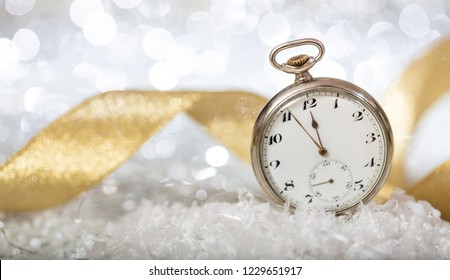 New Years eve countdown. Minutes to midnight on an old watch, bokeh festive background, banner