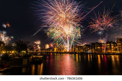 New Year's Eve fireworks in Amsterdam / fire works over a downtown Amsterdam canal / Amstel river