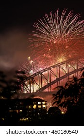 New Years Eve Fireworks on the Sydney Harbour Bridge viewed through some trees at Balls Head Reserve, Sydney.