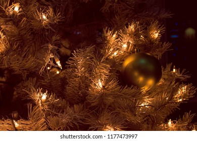 New Year's Eve, night lighting. The Christmas tree is decorated with a garland and balls. Festive, flickering lights. Waiting for the holiday.