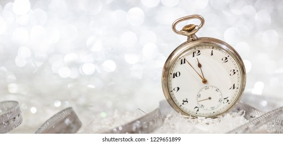 New Years eve party celebration. Minutes to midnight on an old fashioned watch, bokeh festive background, banner