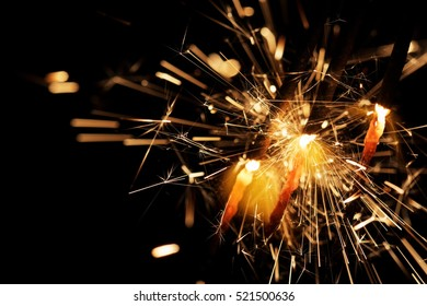 New Years eve sparkler on dark background. Holiday or party fireworks