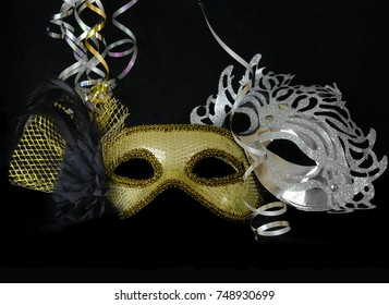 New Year's Eve themed image of gold and silver carnival masks decorated with black flower and feathers with gold ribbons on black background.