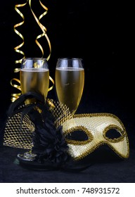 New Year's Eve themed image of gold and silver carnival mask decorated with black flower and feathers with gold ribbons on soft, dark cloth. Two glasses of champagne. Copy space.