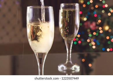 New Year's Eve. Two glasses on the table. Champagne pouring into a glass