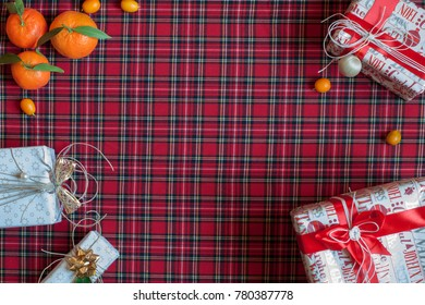 New Year's gifts and Christmas decorations and tangerines on the background of Scottish cloth