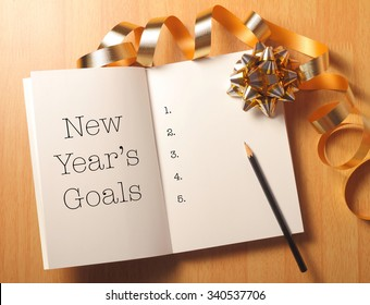 New Year's goals with gold color decorations. New Yearâ??s goals are resolutions or promises that people make for the New Year to make their upcoming year better in some way.