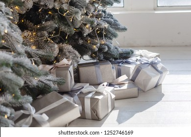 New Year's gold gifts lie under the Christmas tree. Large gift boxes are yellow on the floor. Beautiful Christmas tree in golden toys.