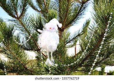 New Year's holidays. A decorative white fluffy snowman hangs on a branch of fresh green spruce.