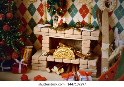 New Year's interior in toy house.  Room with fireplace and Christmas tree for dolls and small toys. Fireplace with a tiny decor.  Miniature toys made hands. Children's needlework