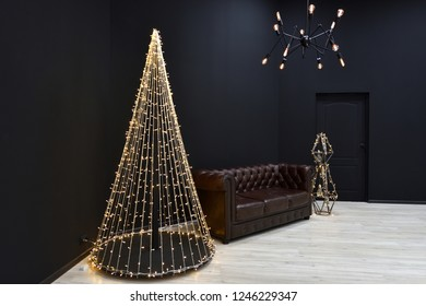 New year's Loft-style decor against a black wall, a Christmas tree from a garland. black chandelier with incandescent lamps and brown sofa. Beautiful New Year's decor with lighting in the studio.