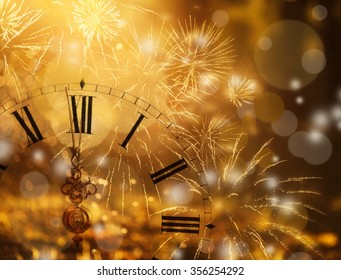 New Year's at midnight - Old clock with fireworks and holiday lights - Shutterstock ID 356254292