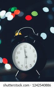 New Year's midnight retro clock face with bokeh lights in background