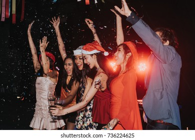 New year's party concept ,Friends party with dj  in the night  club.Group of happy young people throwing confetti and jumping while enjoying dancing together in nightclub