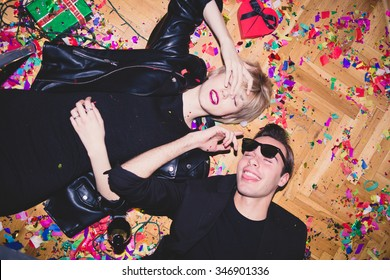 New Year's Party. Girl and boy laying on the floor full of confetti