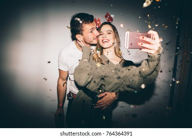 New Year's Party. Girl and boy posing in front of white wall and taking selfie with confetti