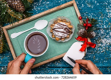New Year's photo of tea with picture of candycane and cakes on table with spruce branches, person writing wishes on postcard