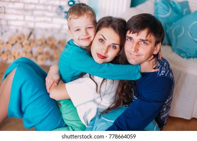 New Year's picture of happy family on background of Christmas decorations. Young parents with their son having fun and smiling on background of Christmas decorations