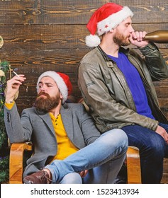 New years resolution. Bad habits to kick before the end of year. Get rid of harmful habits. How to break bad habits. Men drink champagne and smoking. Brutal men celebrate new year near christmas tree.