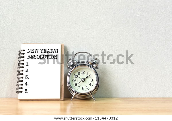 New years resolution concept. Short list to do next year on book and clock vintage on wooden table with white wall